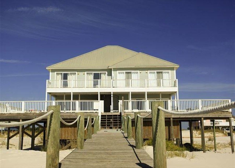 Beachfront rental that has a covered deck and beach boardwalk