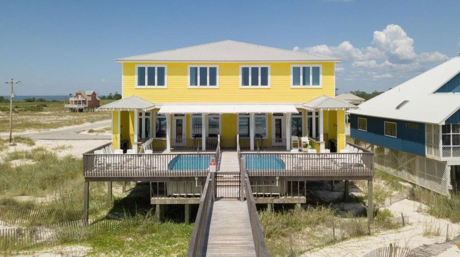 Exterior of yellow multi level Gulf Shore beach house with outdoor pool and deck