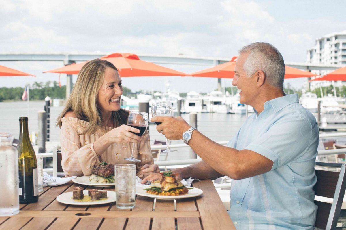 Couple enjoying food and drinks dining outside by the water.