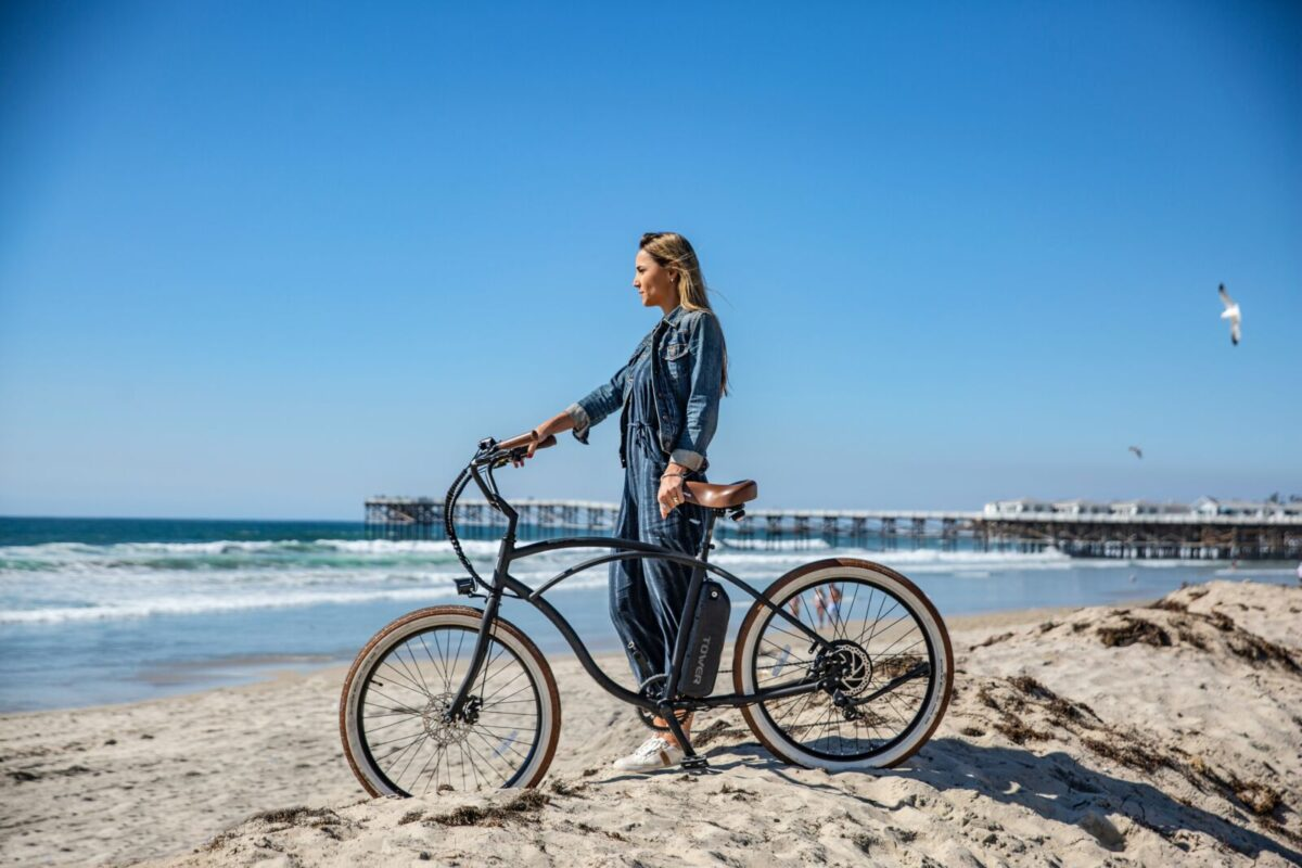 Girl holding bike on the beach